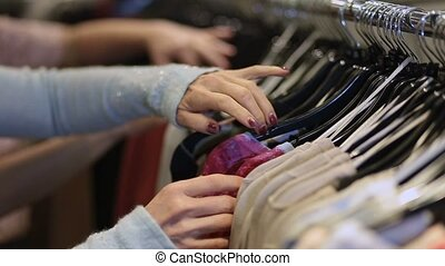 Female hands selecting colorful clothes on hangers - Close...