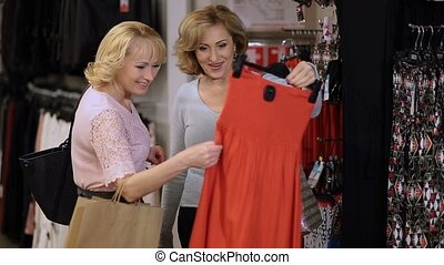 Mature women choosing dress in clothing store - Two...