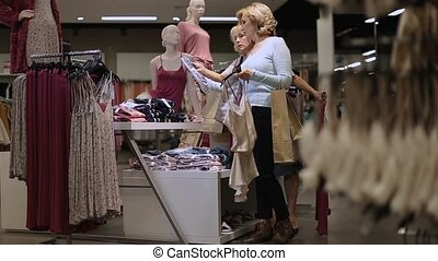 Positive female friends choosing clothes in shop - Positive...