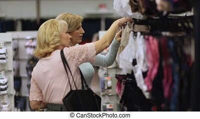 Smiling women doing shopping in clothes store - Senior...