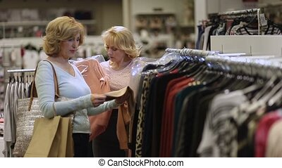 Two women shopping clothes in fashion department -...