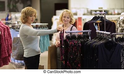 Woman selecting apparel while shopping for clothes -...