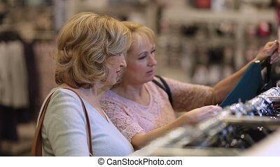 Senior women choosing dress while shopping in shop -...