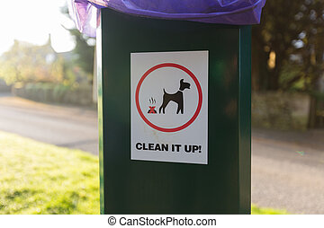 dog waste clean up sign on plastic trash can