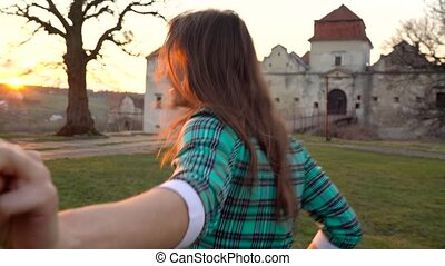 Slow motion follow me - happy young woman pulling guy's hand against the background of an old castle