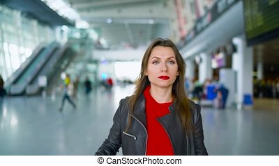 Woman in bright clothes is rolling yellow suitcase in the...