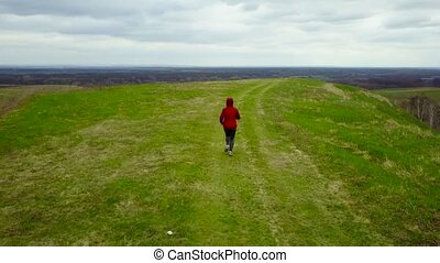Woman is running through the beautiful landscape - the...