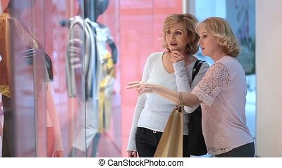 Excited women looking at clothes in store window - Happy...