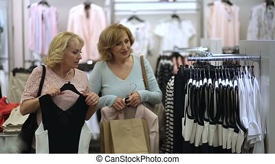 Elegant women looking for dress in clothing store - Elegant...