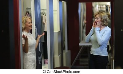 Pretty woman trying new dress in fitting room - Group of two...