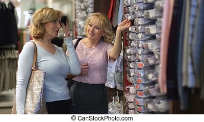 Women looking for right size of male shirt in shop -...