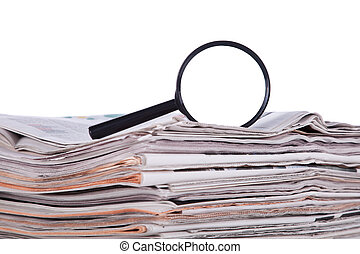 Search for news - Magnify glass over a stack of newspaper to...