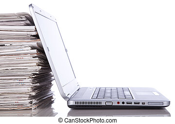 Online News - stack of newspaper next to a laptop isolated...