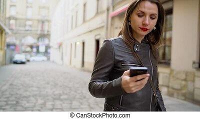 Woman with red lips uses smartphone and strolls along the medieval street