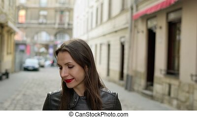 Woman with red lips uses smartphone and strolls along the...