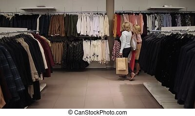 Beautiful shopaholic women buying clothes in store - Adult...