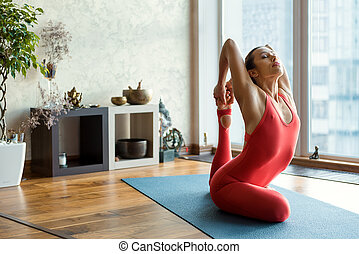 Peaceful young woman doing yoga - Skillful female athlete is...