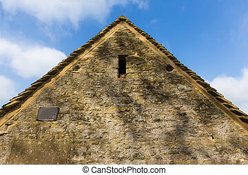 side view of stone wall house in Cotswold, England against...