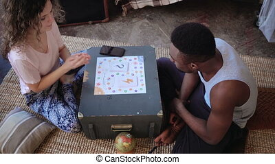 Multiracial couple, man and woman in pajamas playing the...