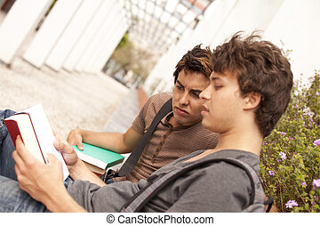 Studing at the school - two young student reading books at...