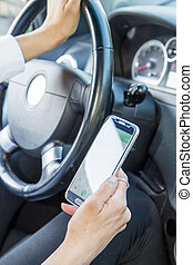 woman looking at cell phone in car
