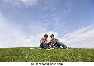 Studing in outdoor - two young student reading books at the...