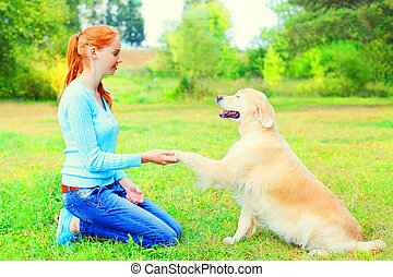 owner woman is training her Golden Retriever dog on the...