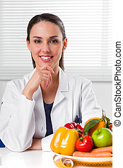Female dietician showing vegetables and fruit - Smiling...