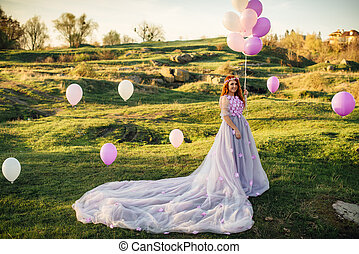 Red-haired woman with balloons in her hand and in a fairy purple dress is standing on the green lawn