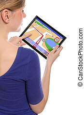 woman holding a touchpad pc, using the navigation programme,...
