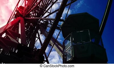 Underside view of a ferris wheel over blue sky - Underside...