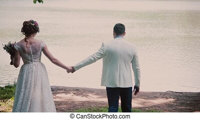 Backview of a happy couple walking on a river bank holding hands on their wedding day. Beautiful white outfits