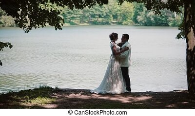 Side view of a kissing couple on their wedding day. Happy bride and groom in a beautiful place on a river bank.