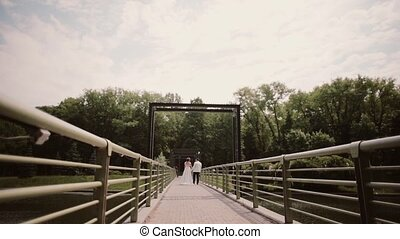 Just married. Backview of a bride and a groom in wedding outfits walking on a bridge holding hands in summertime.