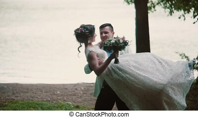 Groom holds his bride in his arms and swirls, bride is happily smiling. Beautiful wedding on a river bank in summertime.