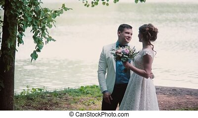Happy couple in love share their wedding day. They stand on a river bank, talk and laugh. Beautiful outfits, bouquet