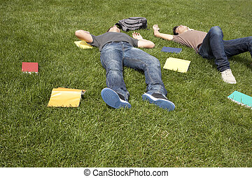 Exhausted with to much study - two young student lying down...