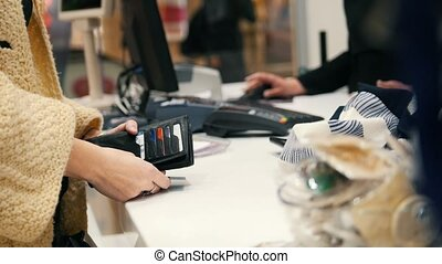 Woman paying by credit card in dress store - shopping...