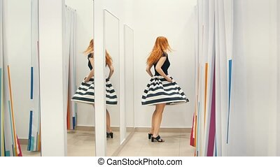 Girl with red hair trying dress near mirror in fitting room...