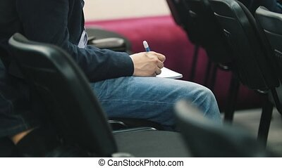 Student in auditorium writes in notebook with pen, close up,...