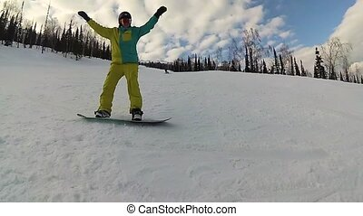 happy guy on a snowboard sliding down the slope at sunny day