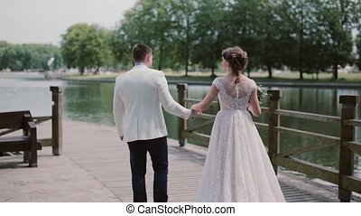Wonderful couple walk on a quay in wedding outfits. They...