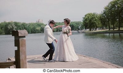 Happy couple on their wedding day dancing and having fun on a quay. River in a park in summertime. Wedding outfits