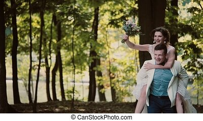 Happy groom is running with his laughing bride on his back....