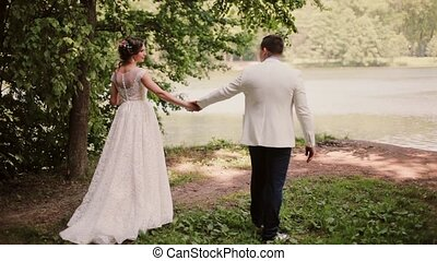 Beautiful couple share wedding day. They walk in park near...