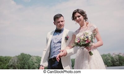 Beautiful bride and handsome groom walk in a park in...