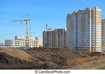 Construction of multistory buildings of white and yellow...