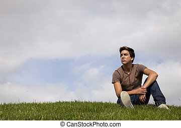Young men future - Young men sited on the grass looking away