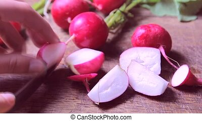 fresh radishes on wooden table, cutting - Girl's hands cut...