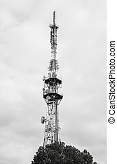 Telecommunications tower against cloudy sky - Black and...